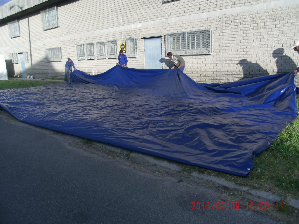 Blue tarpaulin being folded up
